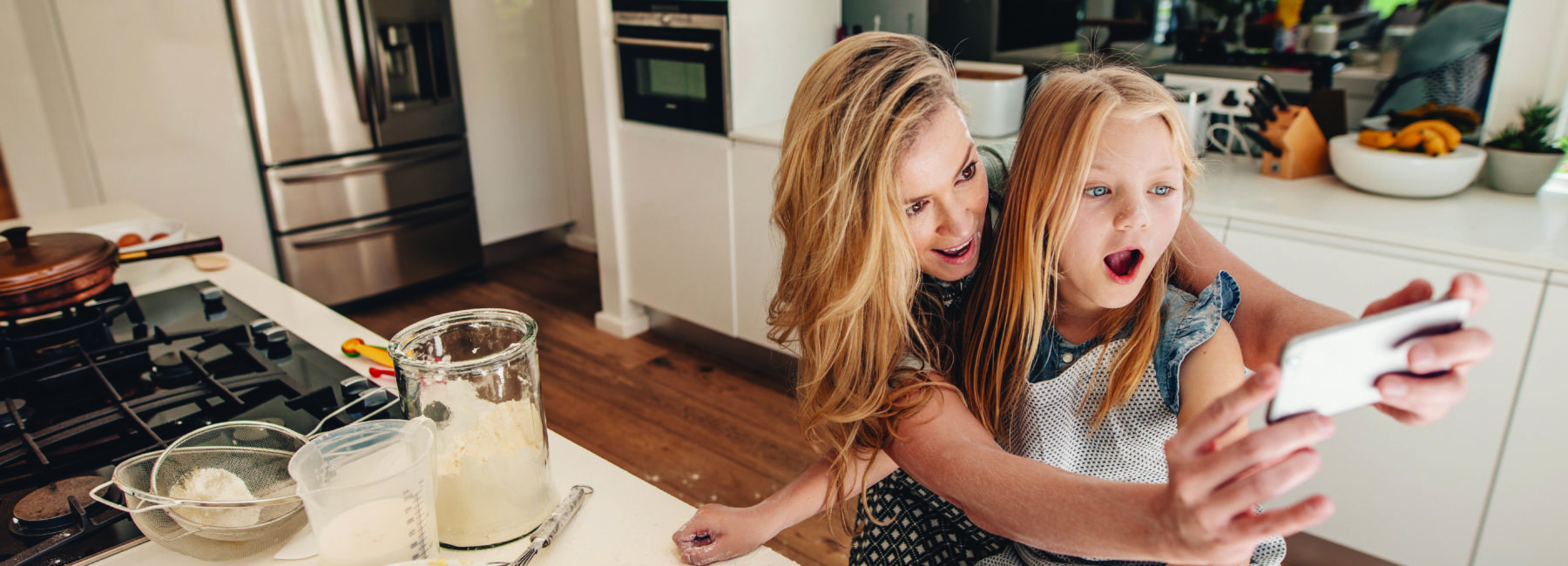 mom and daughter in kitchen taking photo