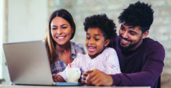 couple with young child looking at laptop