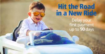 little boy steering toy car