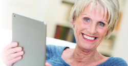 mature woman holding tablet and smiling