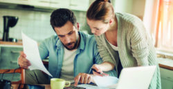 couple reviewing documents and using calculator